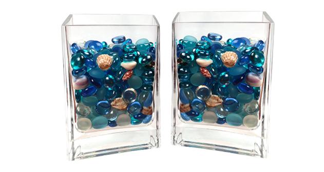 Een mengsel van kleurrijke glaskralen en schelpen in een kleine glazen vaas