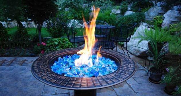 Vuurplaats gevuld met helderblauwe gerecycleerde glasstukjes in de tuin