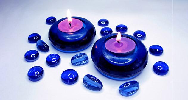 Sprankelende blauwe glaskralen en twee blauwe glazen kandelaars