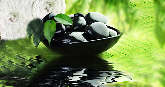 A collection of black polished pebbles in a black bowl shaped vase on a water surface