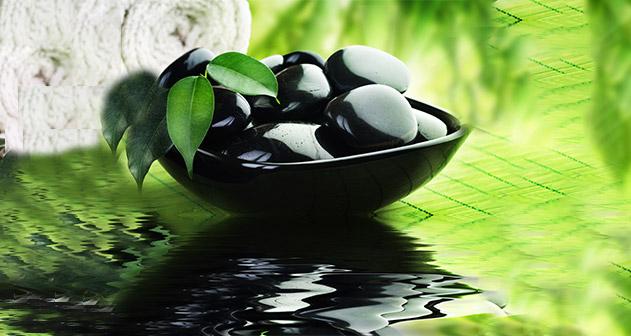 Een verzameling zwart gepolijste kiezels in een zwarte schaalvormige vaas op een wateroppervlak