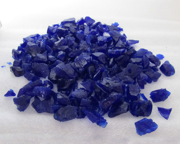 Donkere inktblauwe gerecyclede glasstukjes op witte achtergrond