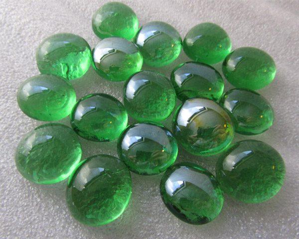 Glanzende groene glaskralen op witte achtergrond