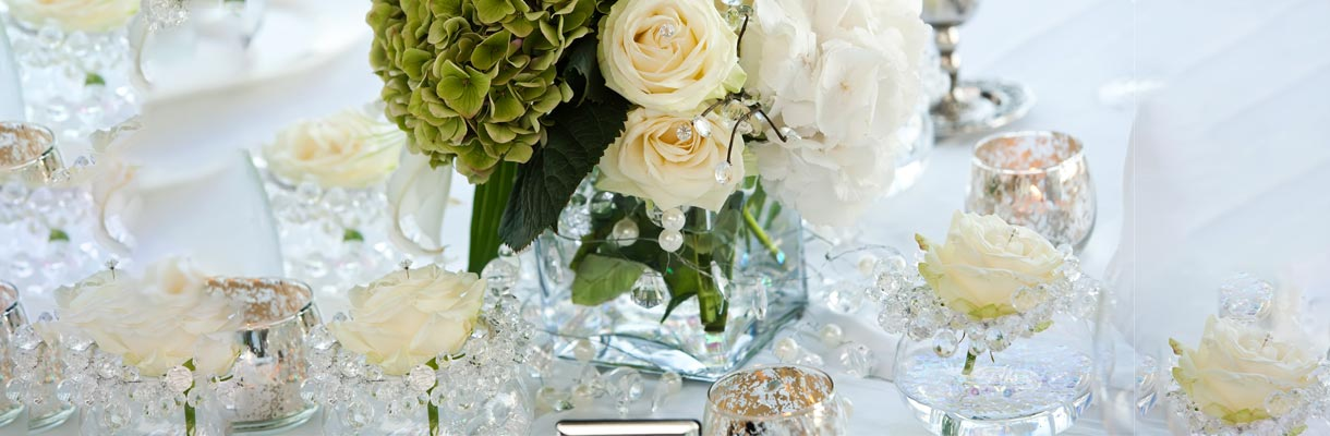 Beautiful white, cream, and green flowers surrounded by small clear glass beads