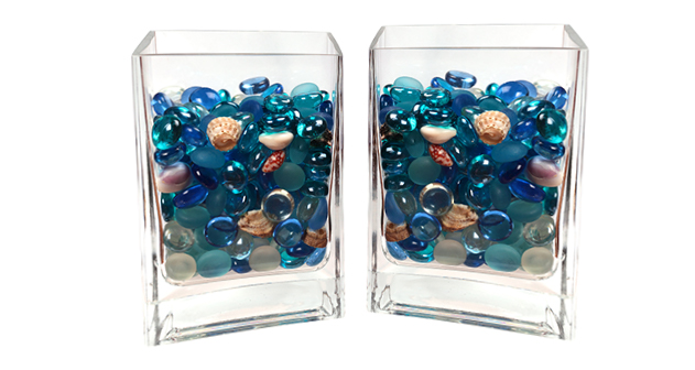 A mixture of colourful glass beads and shells in a small glass vase