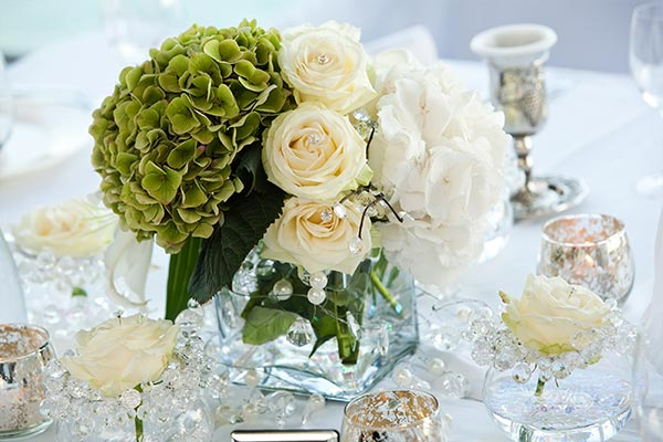 Wedding table design using white flowers surrounded by small clear glass beads