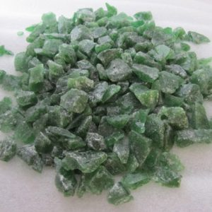 Collection of green recycled glass chippings on white background