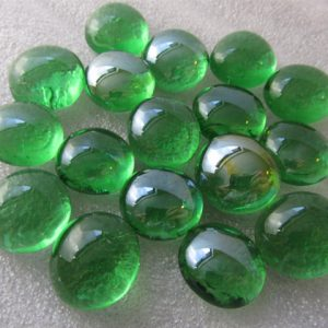 Green glass beads shining on white background