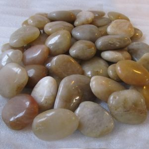 Shiny yellow polished cobble stones on white background