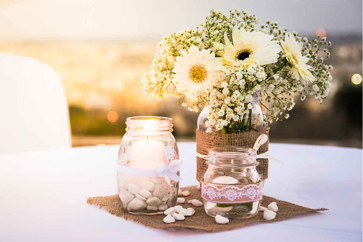 White stone pebbles used in small glass jars for beautiful flower centerpiece