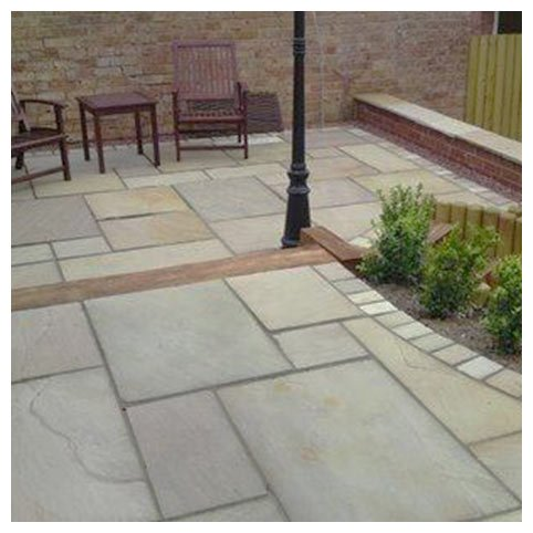 Raj Green paving slabs in back garden with wooden furniture.