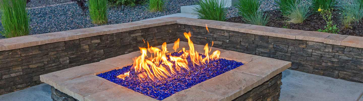 Blue glass chippings in stunning outdoor fire pit surrounded by stone wall bricks and paving stone.