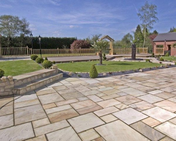 Indian sandstone paving with stunning islands of grass and wooden fence