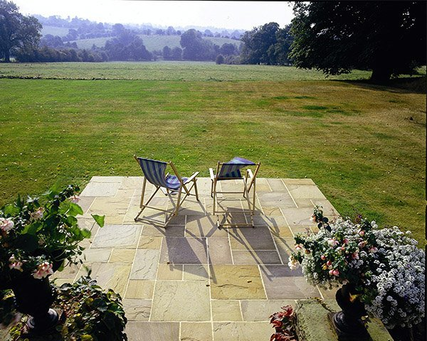Stone Camel Dust Natural Paving with deck chairs looking out on to back garden