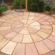 Modak Circle Paving Stone surrounded by stones and flowers