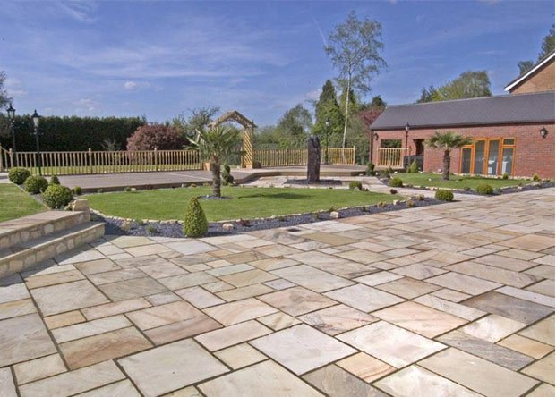 Indian Sandstone Paving neatly placed with islands of grass in the middle