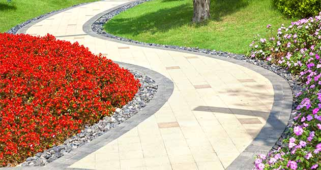 Paving slabs and grey granite cubes used as edging on a garden pathway.